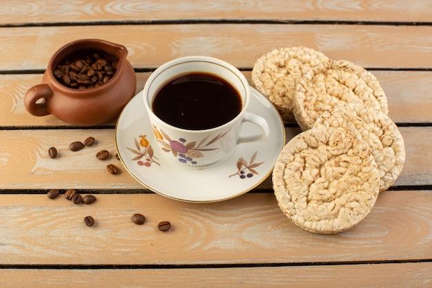 Vista superior de una taza de café caliente y fuerte con semillas de café marrón fresco y galletas en el escritorio rústico crema bebida de semillas de café grano fotográfico