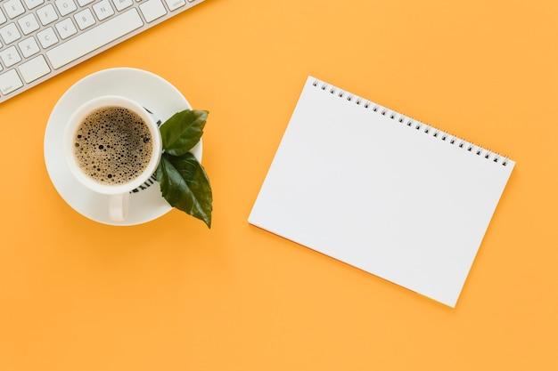 Vista superior de la taza de café y cuaderno