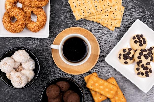 Vista superior de la taza de café con diferentes galletas en la mesa oscura