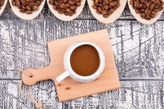Vista superior de la taza de café exprés en una pequeña tabla de madera y los granos de café tostados en la cuchara sobre la superficie de madera blanca