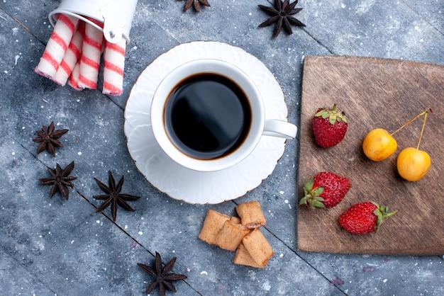 Vista superior de la taza de café con fresas rojas frescas, galletas, dulces de palo rosa en un escritorio brillante, baya de café de caramelo de galleta