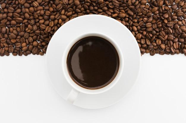 Vista superior taza de café con frijoles tostados