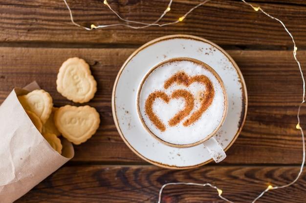 Vista superior de la taza de café y galletas en forma de corazón
