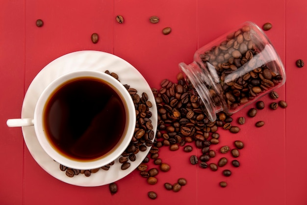 Vista superior de una taza de café con granos de café cayendo de un frasco de vidrio sobre un fondo rojo.