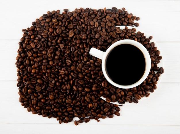 Vista superior de una taza de café y granos de café esparcidos sobre fondo blanco.