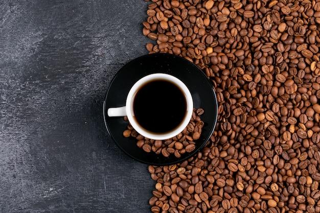 Vista superior de la taza de café y granos de café en la mesa oscura