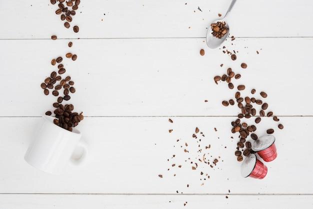 Vista superior taza de café con granos y cápsulas