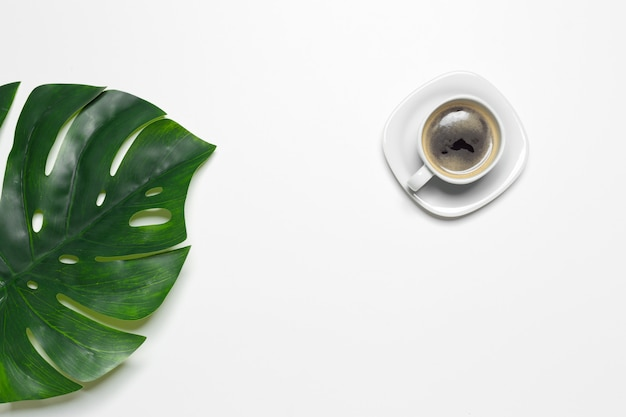 Vista superior taza de café y hoja de monstera