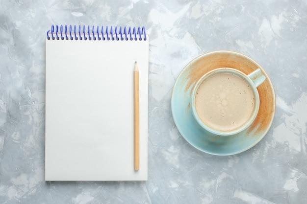 Vista superior de la taza de café con leche dentro de la taza con el bloc de notas en el escritorio blanco beber café leche color del escritorio