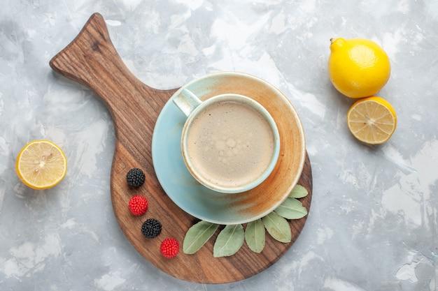 Vista superior de la taza de café con leche dentro de la taza con limones en el escritorio blanco beber café leche escritorio espresso americano