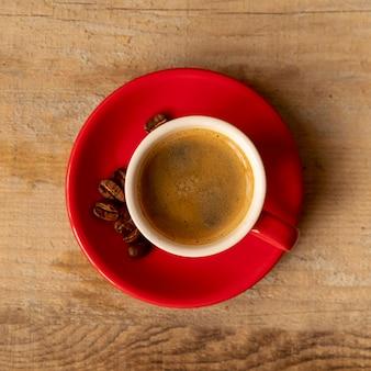 Vista superior taza de café con leche con granos tostados