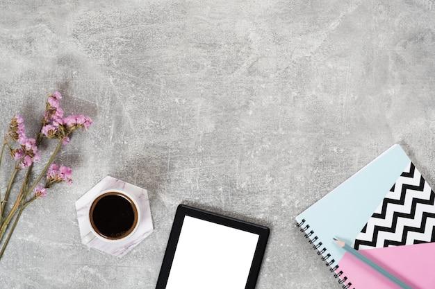 Vista superior taza de café, lector de libros electrónicos, flores, cuaderno de papel sobre superficie de hormigón.