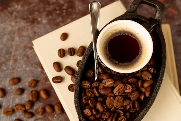 Vista superior taza de café en libros