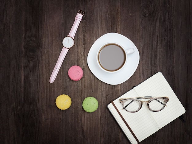 Vista superior de la taza de café, macarons, cuaderno, reloj y gafas. fondo de madera
