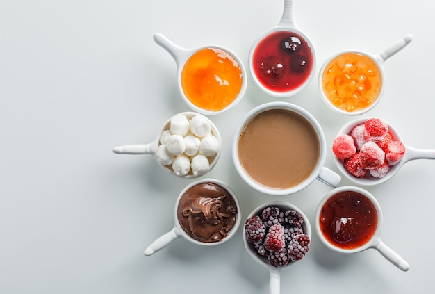 Vista superior de una taza de café con mermeladas, frambuesa, azúcar, chocolate en tazas sobre superficie blanca