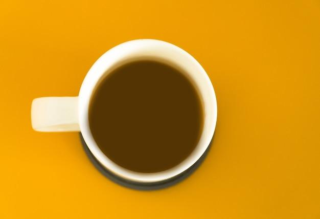 Vista superior de una taza de café negro isolted sobre fondo amarillo.