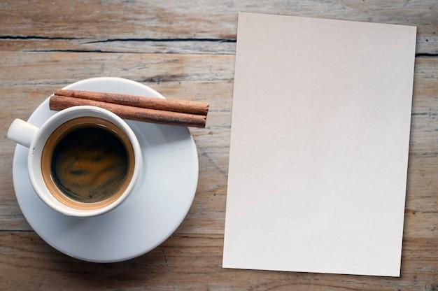 Vista superior de la taza de café y nota de papel en blanco sobre mesa de madera