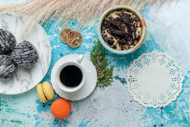 Vista superior de la taza de café con postre de galleta macarons franceses y pasteles de chocolate sobre fondo azul pastel hornear galleta dulce chocolate color azúcar
