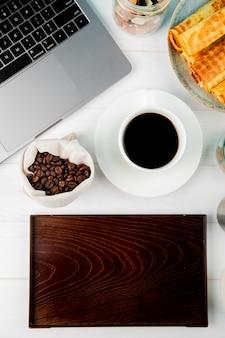 Vista superior de una taza de café con rollos de oblea granos de café en un saco portátil y una tabla de madera sobre fondo blanco.