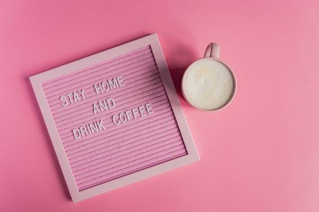 Vista superior de la taza de café rosa con capuchino y qoute quédese en casa y beba café. campaña de auto aislamiento y cuarentena para protegerse de la pandemia
