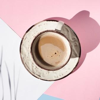 Vista superior taza de café sobre fondo rosa