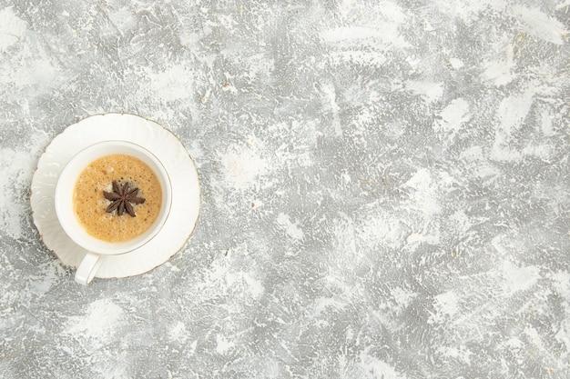 Vista superior de la taza de café sobre una superficie blanca clara