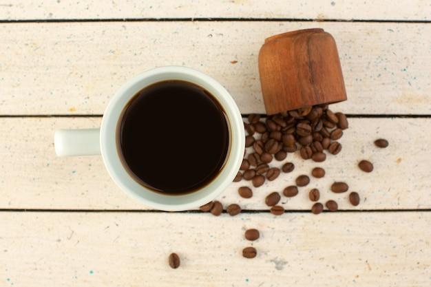 Vista superior de una taza de café en una taza blanca con semillas de café marrón frescas