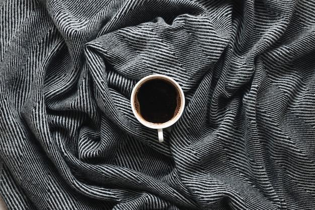 Vista superior de una taza de café en tela de patrón de raya