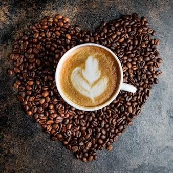 Vista superior taza de capuchino y granos de café en forma de corazón