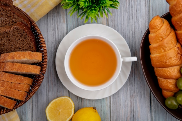 Vista superior de la taza de hot toddy en platillo con rebanadas de pan crujiente de centeno en la canasta y croissants en un tazón con medio limón cortado sobre fondo de madera