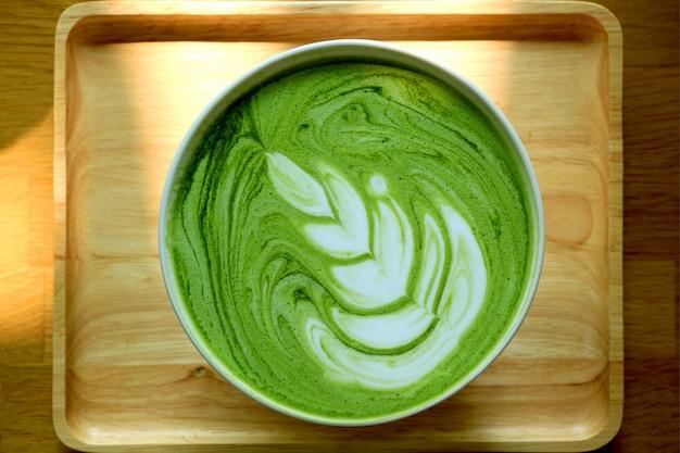 Vista superior de una taza de latte de té verde matcha caliente en bandeja de madera natural