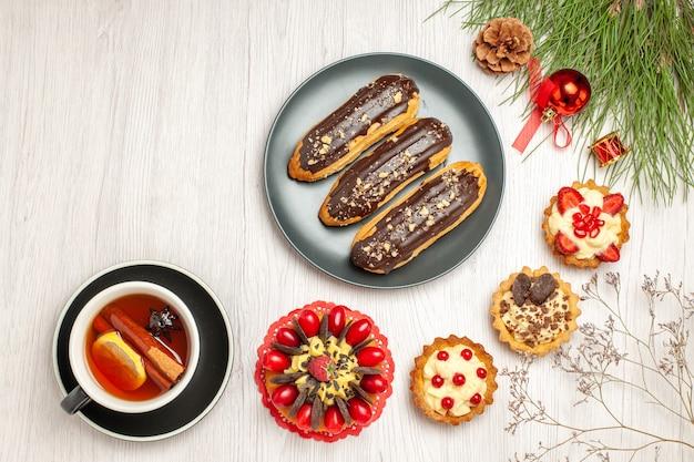 Vista superior de una taza de limón, canela, té, tartas de pastel de bayas, canutillos de chocolate en la placa gris y hojas de pino con juguetes navideños en el suelo de madera blanca