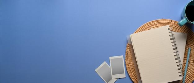 Vista superior de la taza de los marcos de la tarjeta fotográfica del cuaderno en blanco y ritmo de la copia sobre fondo azul claro