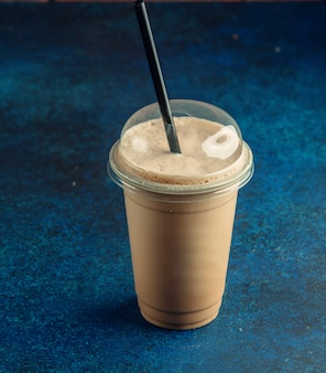 Vista superior de la taza de plástico de café con leche con paja negra