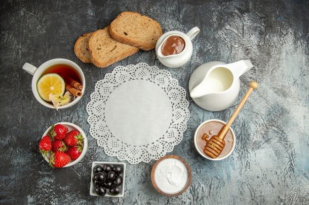 Vista superior de la taza de té con aceitunas y frutas en la superficie oscura de la comida del desayuno de la mañana