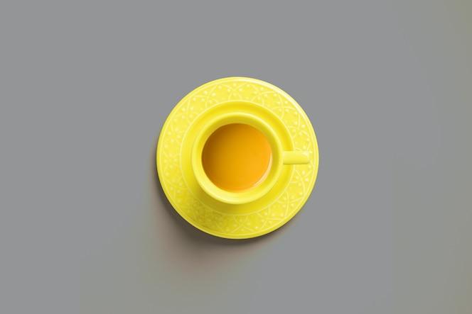 Vista superior de una taza de té amarillo sobre gris