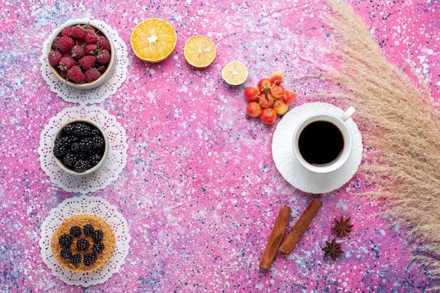 Vista superior de una taza de té con bayas de canela y pastel sobre el fondo rosa claro.