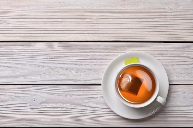 Vista superior de una taza de té con bolsita de té sobre fondo blanco de madera