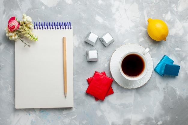 Vista superior de la taza de té caliente dentro de la taza blanca con el bloc de notas de caramelos de chocolate y paquete plateado en el escritorio de luz, beber la hora del té dulce