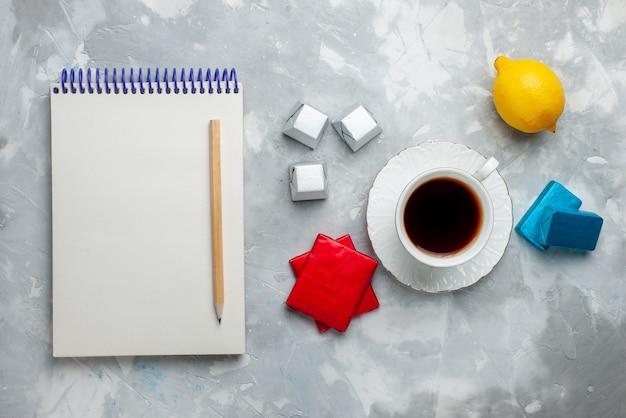 Vista superior de la taza de té caliente dentro de la taza blanca con el bloc de notas de caramelos de chocolate y paquete plateado en el escritorio de luz, beber la hora del té de galletas dulces