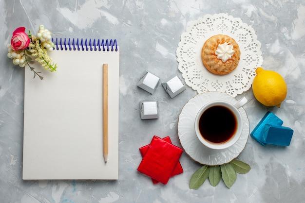 Vista superior de la taza de té caliente dentro de la taza blanca con el paquete de plata y el bloc de notas de caramelos de chocolate en el chocolate de la hora del té de galletas dulces ligeras
