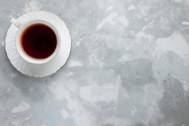 Vista superior de la taza de té caliente dentro de la taza blanca en la placa de vidrio a la luz, bebida de té dulce