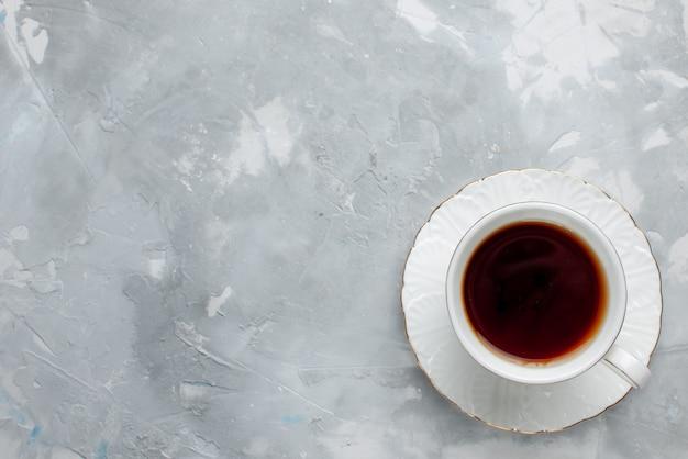 Vista superior de la taza de té caliente dentro de la taza blanca sobre blanco, bebida de té dulce