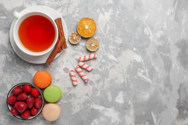 Vista superior de la taza de té con canela y macarons franceses en el escritorio blanco