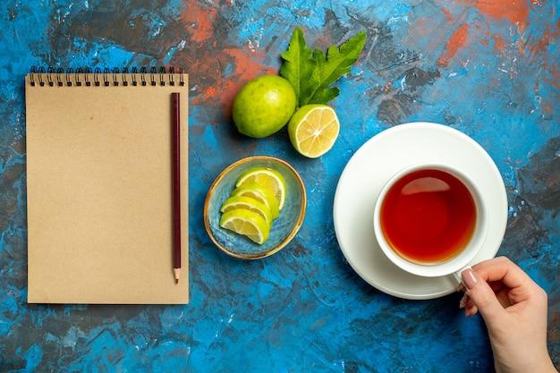 Vista superior de una taza de té cogiendo mano de mujer rodajas de limón un lápiz en el cuaderno sobre la superficie azul roja