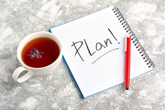 Vista superior de la taza de té con cuaderno y lápiz sobre la superficie blanca