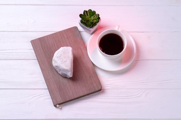 Vista superior de la taza de té con cuaderno y plan. fondo de escritorio blanco.
