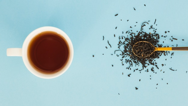 Vista superior taza de té con cuchara llena de hojas secas