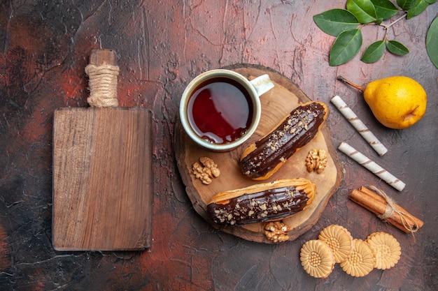 Vista superior de una taza de té con deliciosos canutillos de chocolate en un pastel de galleta dulce de mesa oscura
