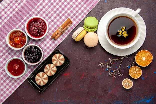 Vista superior de la taza de té dentro de la placa y la taza sobre fondo oscuro bebida de té dulce de fotografía en color
